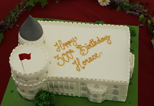 """color photo of cake made in the shape of Strawberry Hill with writing """"Happy 300th Birthday, Hora""""ce"""