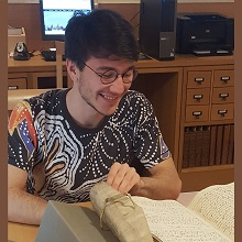 Photo of Elliot Briery, a young man with dark hair and glasses, seated at the table in the LWL Reading Room, looking at a limp vellum-bound manuscript volume of Letters from the Levant Company