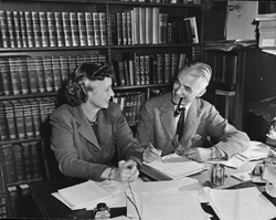 black and white photo or a couple (Annie Burr Lewis and Wilmarth Sheldon Lewis) seated next to each other at a desk, looking at each other, with a wall of books on shelves behind them.