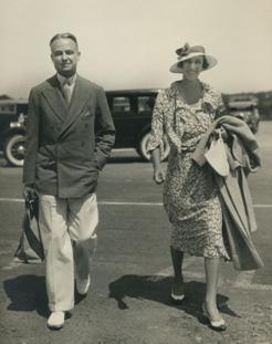 a 1930s black and white photo or W.S. Lewis and Annie Burr Lewis walking side by side toward the camera with a car parked behind them.