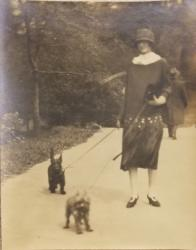 B/w photo of young woman in 1920s dress with 2 dogs on leashes