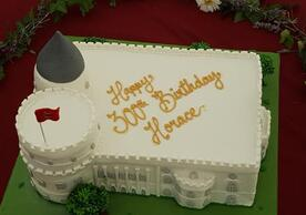 "color photo of cake made in the shape of Strawberry Hill with writing ""Happy 300th Birthday, Hora""ce"