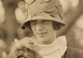 Portrait photo of young woman in 1920s hat holding fluffy dog