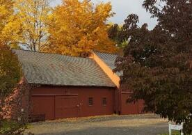 color photo of a red barn with golden autumn leaves on trees behind