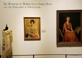 color photo of main wall of exhibition with two portrait paintings, one is Mrs. Lewis