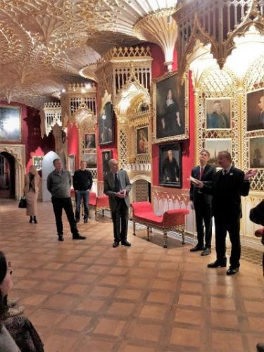 color photo of people standing in a long room with elaborate gothic ceiling and paintings